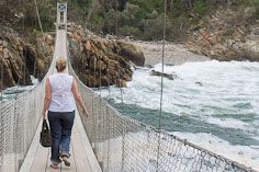 The final section of a three-span pedestrian suspension bridge stretches across the mouth of the Storms River.