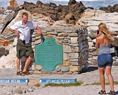 A tourist poses at the southern most tip of the African Continent, at L'Cape Agulhas.