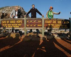 Tourists have their pictures snapped at the Cape of Good Hope sign at the southern point of the Cape Peninsula near Cape Town.