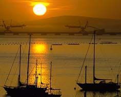 The sun sets over moored yauchts and the iron-ore export jetty at Saldanha Bay Harbour.