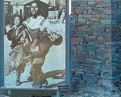 Part of the Hector Pieterson Memorial in Soweto, South Africa. A news photograph of Hector's limp body being carried away after being shot by police is visible.