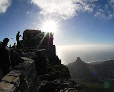 Visitors take in the view from atop Table Mountain as the sun sets over Lions Head and Cape Town below.