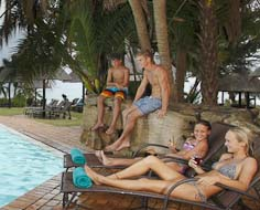 Kids enjoying the swimming pool at the Wild Coast Sun with the Indian Ocean in the background.