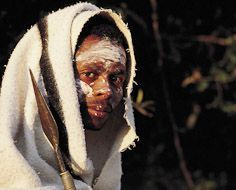 A Xhosa intiate with white clay on his face, a traditional blanket and spear.